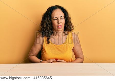 Beautiful middle age woman wearing casual clothes sitting on the table with hand on stomach because indigestion, painful illness feeling unwell. ache concept.