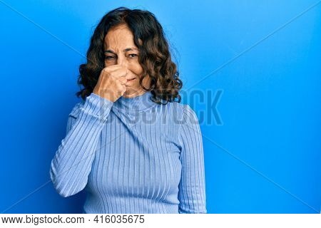 Middle age hispanic woman wearing casual clothes smelling something stinky and disgusting, intolerable smell, holding breath with fingers on nose. bad smell