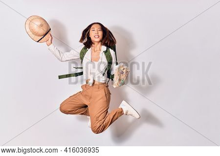 Young beautiful chinese backpacker girl wearing backpack smiling happy. Jumping with smile on face holding city map and hat over isolated white background