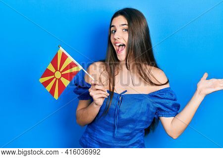 Young brunette teenager holding macedonian flag celebrating achievement with happy smile and winner expression with raised hand