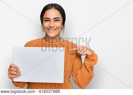 Young brunette woman holding blank empty banner pointing finger to one self smiling happy and proud