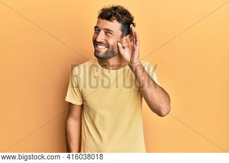Handsome man with beard wearing casual yellow tshirt over yellow background smiling with hand over ear listening an hearing to rumor or gossip. deafness concept.
