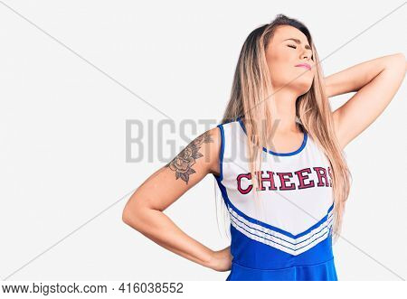 Young beautiful blonde woman wearing cheerleader uniform suffering of neck ache injury, touching neck with hand, muscular pain