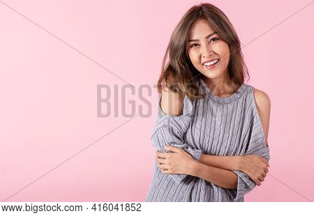 Portrait Of A Young Asian Woman Smiling Happily. Her Clean Skin And White Teeth Isolated On A Pink B