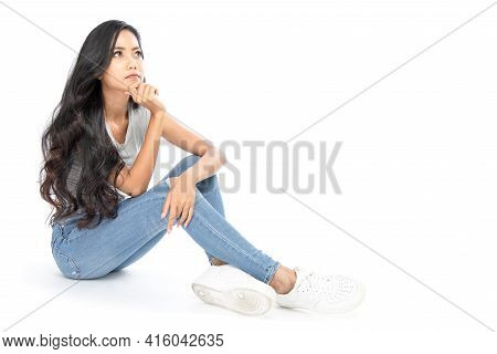 A Young Asian Woman Wore A Casual Dress Sit On The Floor. She Looks At The Copy Space On The Top. Sh