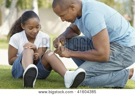 African American father applying bandaid to daughter outdoors