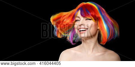 Woman hair as color splash. Rainbow up do short haircut. Beautiful young girl model with glowing  healthy skin on a black background