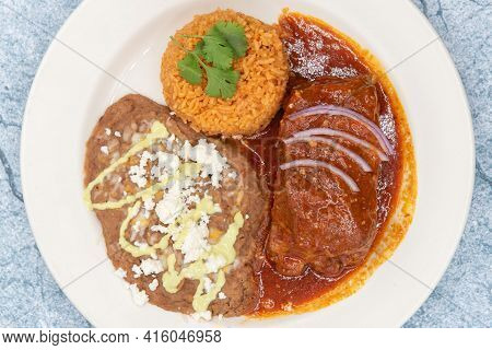 Overhead View Of Large Slap Of Chile Colorado Entree Meat, Refried Beans, And Rice Drenched In The R