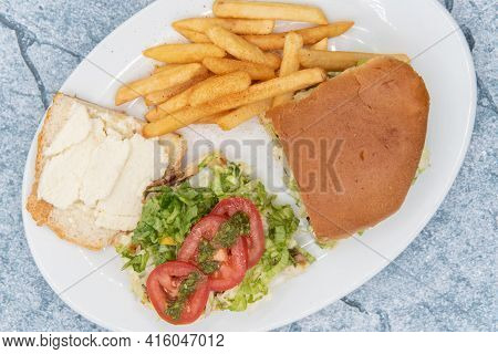Overhead View Of Large Churrasquito Sandwich Lies Open With Juicy Tomato Slices On Top Served With F