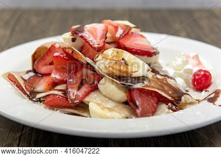 Mouthwatering Plated Of Crepes Piled With Sliced Bananas And Strawberrries Topped With Whipped Cream