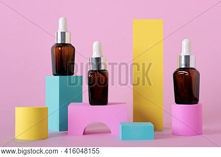 Beauty Natural Skincare Product Mock Up. Serum Or Collagen Dropper Bottles On Different Geometric Po