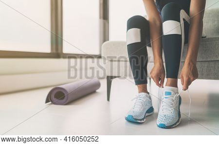 Woman tying running shoes laces getting ready to get back in shape going to yoga or pilates fitness class training at home.