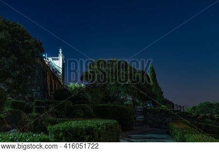 Landscape Of Night Park On Sea Shore With Clear Sky With Moon Over, Dark Tone. The Walls And Towers
