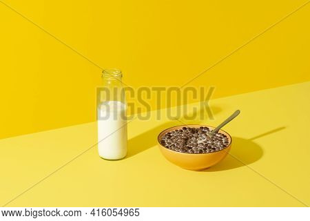 Bowl With Cereals And A Glass Bottle Of Milk On A Yellow Table In Bright Light. Breakfast Table With