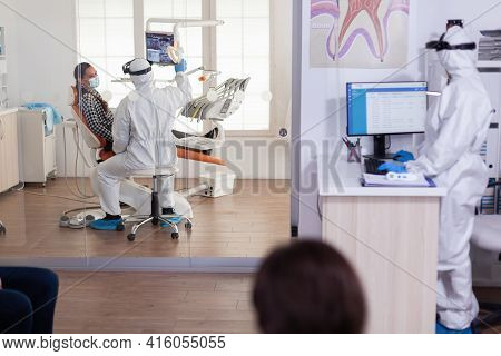 Stomatologist In Protective Suit Asking Patient Teeth Problems