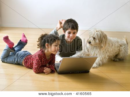 Two Kids With Laptop Computer And A Dog
