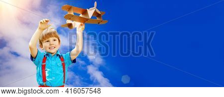 Kids fantasy. Child playing with toy airplane against sky and clouds background. Care of childrens dreams.