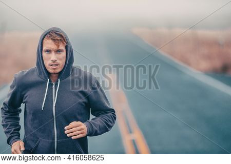Morning run endurance runner athlete running outside in cold winter training cardio. Man breathing while jogging outdoors in hoody.