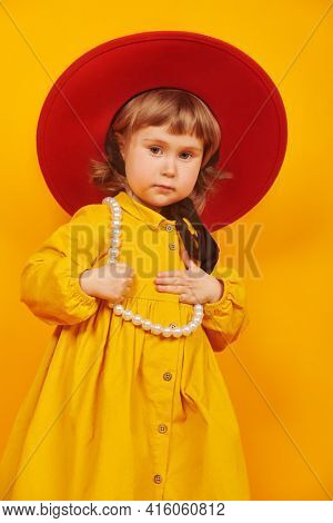 Cute little girl fashionista. Portrait of a lovely little girl in red hat and yellow dress on a yellow background.
