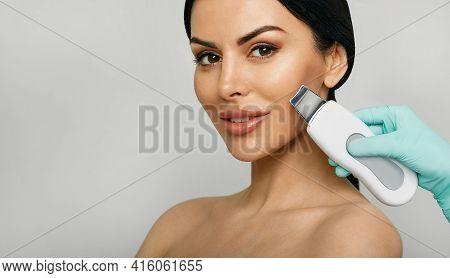 Ultrasonic Facial Peeling. Mixed Race Womans Face During Ultrasonic Peel Skin Procedure Over Gray Ba