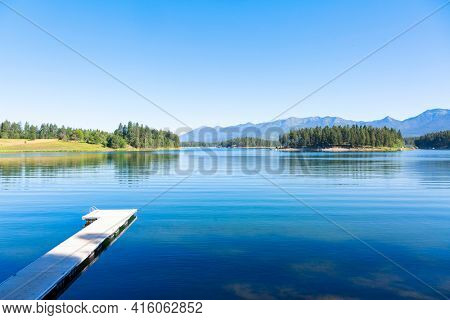 A calm beautiful scenic lake high in the Mountains of Montana called Echo Lake. A landscape photo that shows the beauty of Montana. Blue serene waters with a boat dock