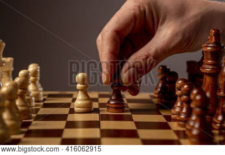 Male Hand Moving Pawn On Chess Board, Starting Game. Making Business Decision Concept