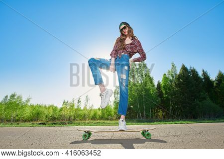 Cool modern teen girl rides a longboard on a highway outside the city. The spirit freedom and autumn adventures.