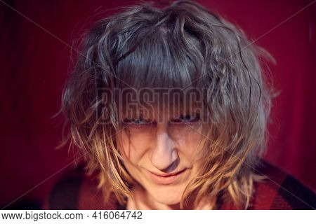 Portrait Of Tousled Disheveled Middle-aged Woman Looking Like A Madwoman On Red Background In Studio