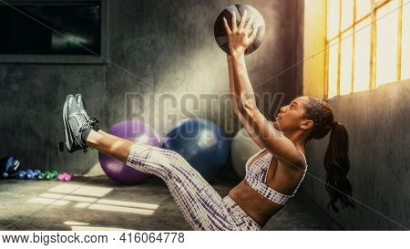 Woman weightlifting with a medicine ball in the gym wallpaper