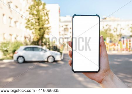A Woman Holds A Cellphone With Mock Up, Hand Close-up. In The Background Is A City Street With Car.
