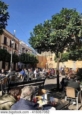 Seville, Spain - December 23, 2019: People Enjoying The Sun In The Small Square Of San Andres, In Ou