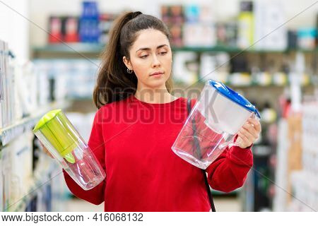 Portrait Of Young Woman Chooses Between Two Carafe With A Water Filter In A Home Appliance Store. Th