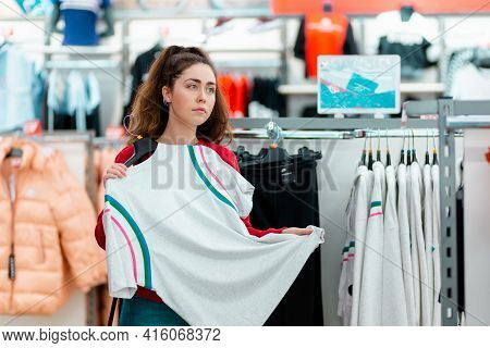 Portrait Of A Young Pensive Woman Choosing White T-shirt In A Store. The Concept Of Shopping And Con