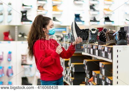 Consumerism. Portrait Of Young Caucasian Woman In A Medical Mask Chooses Shoes In A Store. Side View