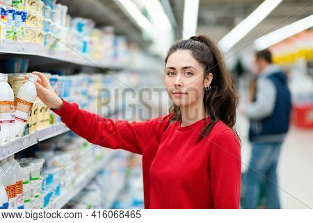 Portrait Of A Young Pretty Woman Choosing Dairy Products In A Supermarket Refrigerator. The Concept