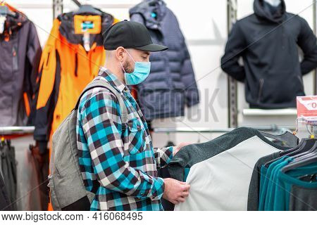 Antiviral Protection In Public Places. A Man In A Medical Mask Chooses Clothes In A Store. Side View