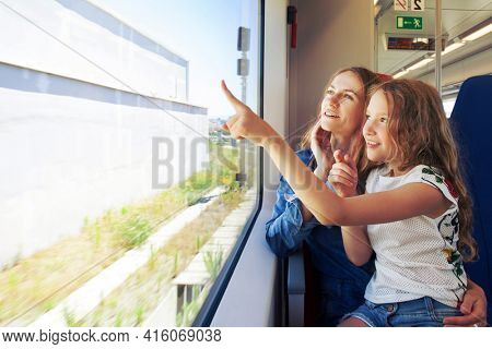 Woman with child traveling by pablic transport. Family travelling in a train and looking through the window