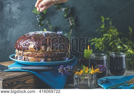 Woman Hand Is Decorating Delicious Homemade Cake, Served On Wooden Table. Chocolate Cake Food Photog