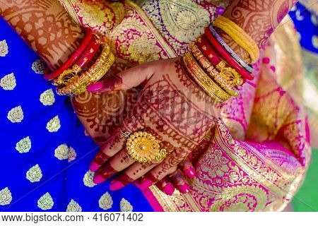 Hindu Bengali Indian Bride Crossing Hands That Has Beautiful Mehndi Decoration And Expensive Gold Je