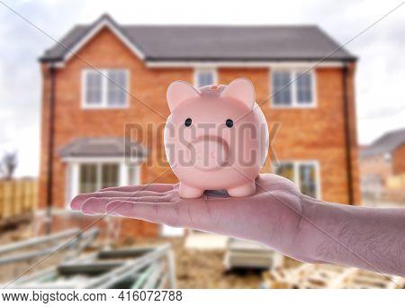 A Hand Holding Piggy Bank Against Blurred Semi-detach House