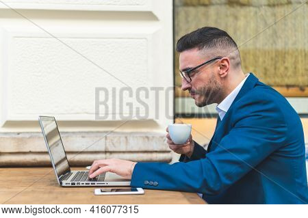 Businessman Using Laptop While Drinking Coffee In A Cafe.