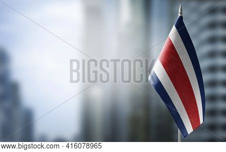 A Small Flag Of Costa Rica On The Background Of A Blurred Background