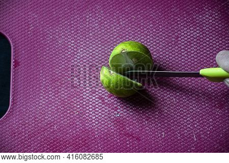 Stock Photo Of Women Cutting Fresh Juicy Lemon On Purple Color Chopping Board With Yellow Color Knif