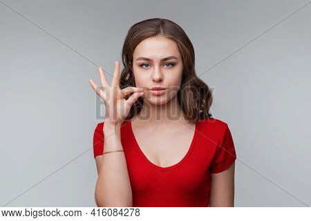 Your Secrets Safe With Me Concept. Young Brunette Woman Showing Zip Gesture As If Shutting Mouth On