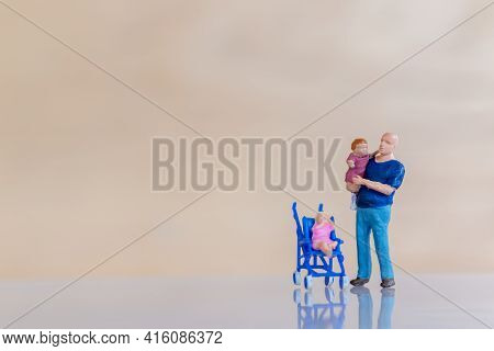 Miniature People Father Holding Their Cute Baby Daughter In The Arms, Father's Day Concept.