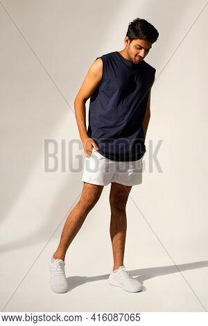 Man in navy tank top and shorts sportswear apparel full body