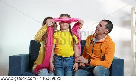 Happy Family At Home. Parents And Child A Playing Blindfold Game. Happy Family Playing Together At H