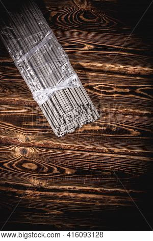 Open Pack Of Welding Electrodes On A Wooden Background. Studio Photo In Hard Light.