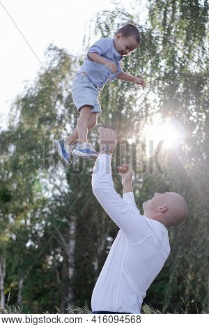 Bald Dad Tosses Up Son In The Field Or Forest On Sunny Summer Day. Father\'s Day.