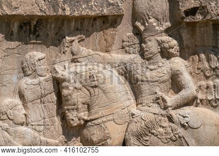 Murals Of Necropolis, King Burial Site Of Ancient Persia. King On His Horse Carved Into Sandstone Ro